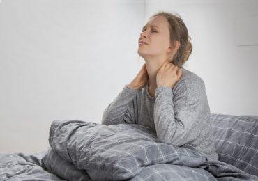 אישה במיטה עם כאבים